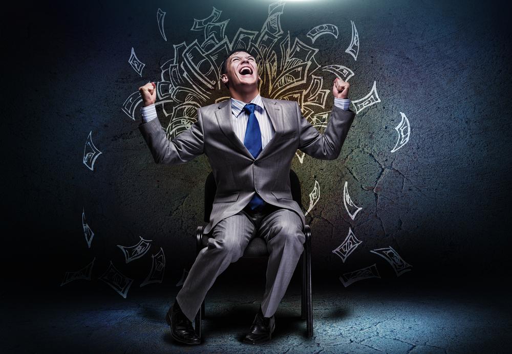 Joyful businessman sitting on chair under money rain